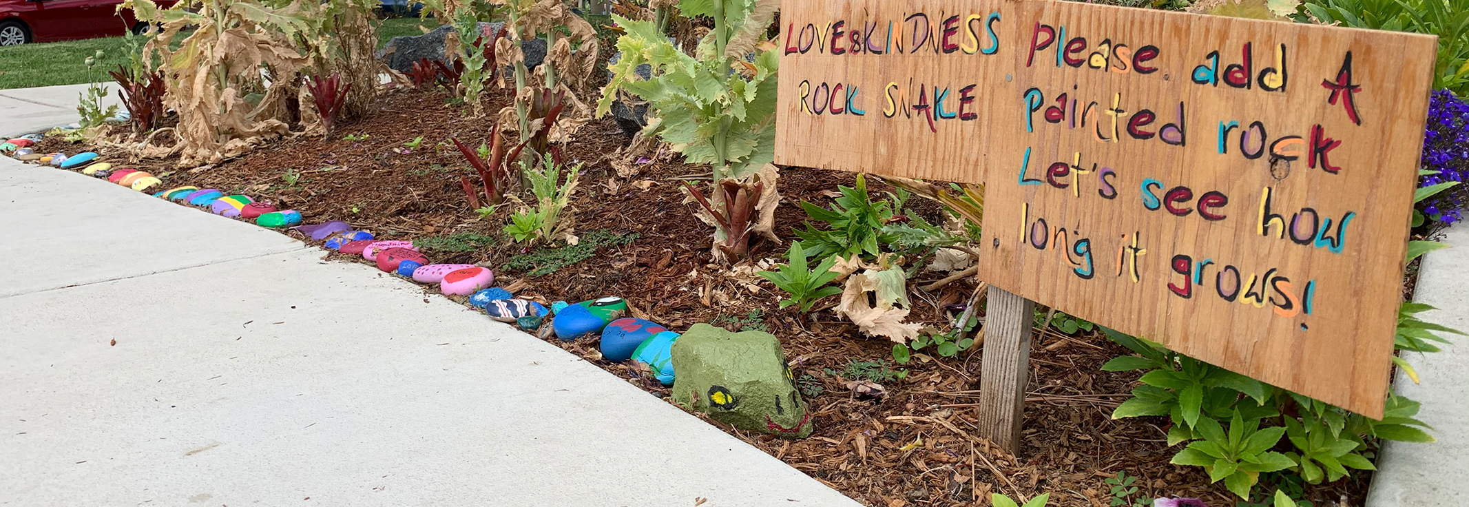 Colorful painted rocks lined up to form a snake in the garden outside UCI Extended Day Care Center. Sign reads Love and Kindness Rock Snake Please add a painted rock Let's see how long it grows!