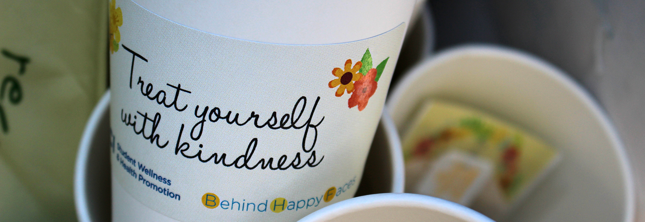 Close up of a coffee cup sleeve that says Treat yourself with kindness with branding for Behind Happy Faces and Student Wellness & Health Promotion