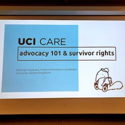 """Projector screen with title slide of a presentation: """"UCI CARE advocacy 101 & survivor rights"""""""